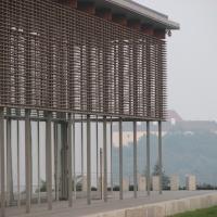 Fassade aus Holzlamellen im Hintergrund die Burg